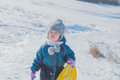 Am Schneehügel geht das Kind mit dem Schlitten stockfotografie