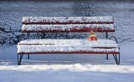 Schneekugel auf Bank mit Schnee Stockfoto