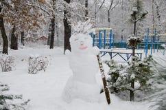 Schneemann auf dem Hintergrund des Sportplatzes stockbild