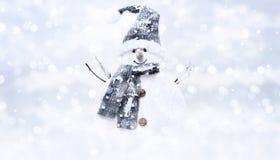 Schneemann auf dem unscharfen hellen Weihnachtslichthintergrund, grüßend Stockfotografie