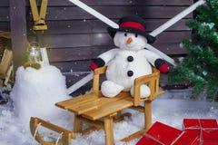 Schneemann auf einem hölzernen Pferdeschlitten Stockbilder
