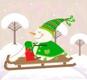 Schneemann auf einem Schlitten Stockbild