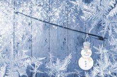 Schneemann befestigt zum Violinenbogen, Blau, hölzerner Hintergrund Winterzeitschneeflocken herum Lizenzfreie Stockfotos