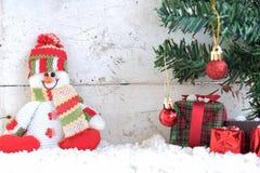 Schneemann, der auf dem Schnee mit Weihnachtsbaum im Weinlesehintergrund sitzt Lizenzfreie Stockbilder