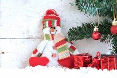 Schneemann, der auf dem Schnee mit Weihnachtsbaum sitzt Lizenzfreie Stockfotos