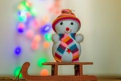 Schneemann, der auf einem Schlitten sitzt Stockfotografie