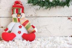 Schneemann, der auf Schnee sitzt Stockfotografie