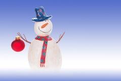 Schneemann, der eine Weihnachtsverzierung hält Stockfotos