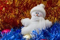 Schneemann, der in Weihnachtsbaum lametta legt Stockfoto