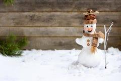 Schneemann mit einem Besen auf einem hölzernen grauen Hintergrund Lizenzfreie Stockbilder