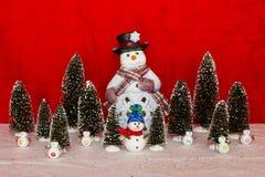 Schneemann mit kleinem Schneemann und Bäumen Lizenzfreie Stockfotografie