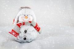 Schneemann mit warmer Kleidung im Schnee Stockbild