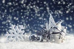 Schneemann mit Weihnachtsdekoration und -verzierungen - Klingelglocken spielen Schneeflocken in der schneebedeckten Atmosphäre di Stockbild