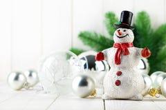 Schneemann mit Weihnachtstanne und -bällen Stockfotografie