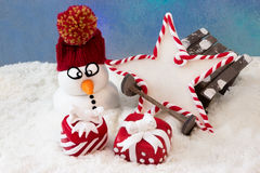 Schneemann nahe bei einem Schlitten Stockbild