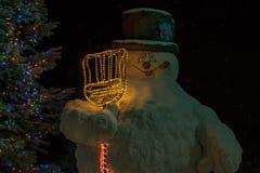 Schneemann neben einem Weihnachtsbaum nachts stockfotos