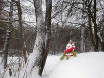 Schneemann sitzt auf dem Schneehügel Stockbild