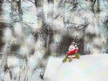 Schneemann sitzt auf dem Schneehügel Lizenzfreie Stockfotografie