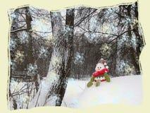 Schneemann sitzt auf dem Schneehügel im forrest Stockfotos