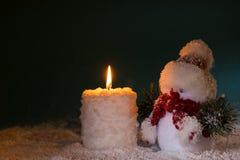 Schneemann- und Brandkerze auf dunklem Hintergrund Stockfoto