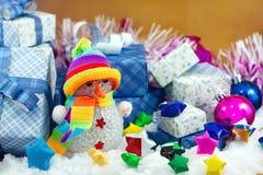 Schneemann und Geschenkbox mit kleinem Sternpapier auf dem Schneefeld Lizenzfreie Stockfotografie