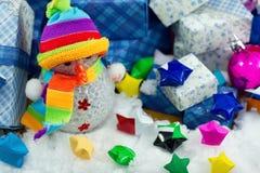 Schneemann und Geschenkbox mit kleinem Sternpapier auf dem Schneefeld Lizenzfreies Stockfoto