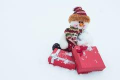 Schneemann und Geschenke auf dem weißen Schnee Lizenzfreie Stockfotos