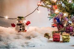 Schneemann und Glühlampe stehen unter Stapel des Schnees nachts stille Nacht, frohe Weihnachten und guten Rutsch ins Neue Jahr Lizenzfreie Stockfotografie