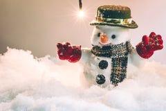 Schneemann und Schnee fällt unten, Stand unter Stapel des Schnees nachts stilles mit einer Glühlampe Lizenzfreie Stockfotografie