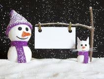 Schneemann und Schneekatze mit Zeichen Lizenzfreie Stockfotografie