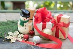 Schneemann, Weihnachtsgeschenk und Verzierung über Holztisch Stockbilder
