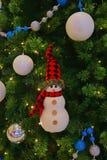 Schneemann wenig weiches Spielzeug mit glänzenden Bällen verzieren das Hängen am grünen Weihnachtsbaumhintergrund Stockbild