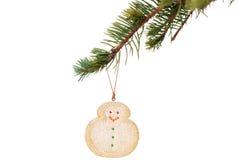 Schneemannplätzchen, das am Weihnachtsbaumzweig hängt Stockfoto