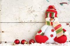 Schneemannpuppe, die auf dem Schnee mit Weihnachtsball sitzt Lizenzfreie Stockbilder