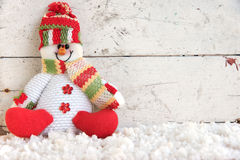 Schneemannpuppe, die auf Schnee sitzt Stockbilder