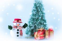 Schneemannstand nahe Geschenkbox auf weißem Hintergrund Stockfotos