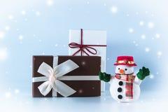 Schneemannstand nahe Geschenkbox auf weißem Hintergrund Stockbild