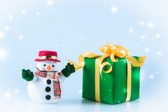 Schneemannstand nahe Geschenkbox auf weißem Hintergrund Stockfotografie