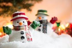 Schneemannstand unter Stapel des Schnees nachts stilles mit einer Glühlampe, leuchten der Erwartungsfreude und dem Glück in den f Stockfotografie
