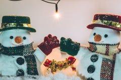 Schneemannstand unter Stapel des Schnees nachts stilles mit einer Glühlampe, leuchten der Erwartungsfreude und dem Glück in den f Lizenzfreie Stockfotografie