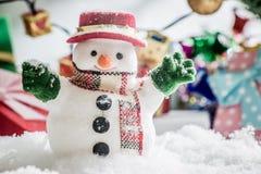 Schneemannstand unter Stapel des Schnees nachts stilles mit einer Glühlampe, leuchten der Erwartungsfreude und dem Glück in den f Stockfoto