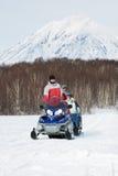 Schneemobil fahrung mit Touristen im Pferdeschlitten fährt auf Hintergrund des Waldes und des Vulkans Lizenzfreies Stockbild