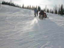 Schneemobil fahrung und Skifahrer Lizenzfreie Stockbilder