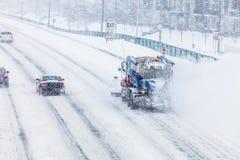 Schneepflug, der den Schnee von der Landstraße während eines Schneesturmes entfernt Lizenzfreie Stockfotografie