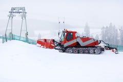 Schneepflug, der an einer Skisteigung arbeitet Stockfotografie