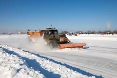 Schneepflug säubert eine Straße, die mit Eis bedeckt wird Stockfotografie