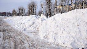 Schneereinigung im Winter in der Stadt Große Stapel des Schnees sammelten durch Autos auf dem Straßenrand Geklärter Asphalt für A Lizenzfreies Stockfoto