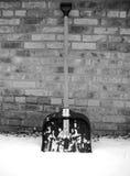 Schneeschaufel im Schnee auf einem Hintergrund einer Backsteinmauer Stockfoto