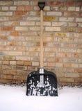 Schneeschaufel im Schnee auf einem Hintergrund einer Backsteinmauer Stockfotografie