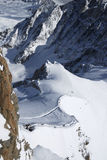 Schneesteigung mit Skifahrern zwischen Gebirgszügen stockfotografie
